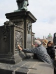 Rubbing the brass plaque on the Charles Bridge. A tradition.